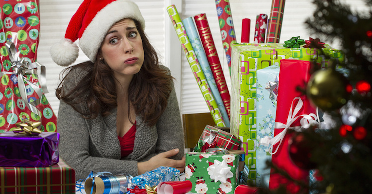 Woman wrapping Christmas presents, looking exhausted.